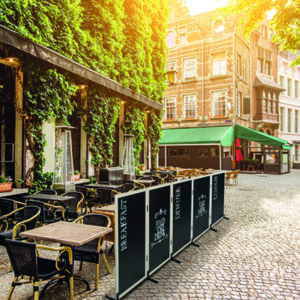 Kreidetafel mit Holzrahmen in weiss, aufgestellt vor einem Restaurant als Werbung und Sichtschutz