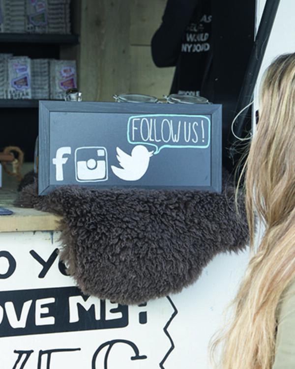 schwarze Kreidetafel mit Holzrahmen aufgestellt in einem Foodtruck, Follow us Beschriftung