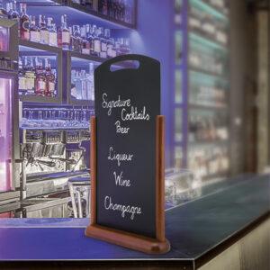 Tischtafel beschriftet mit Kreidemarker und aufgestellt in einer Bar