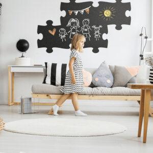Bemalte Kinder Wandtafel Puzzle Form SIlhouette aufgehängt im Kinderzimmer von einem kleinen Mädchen