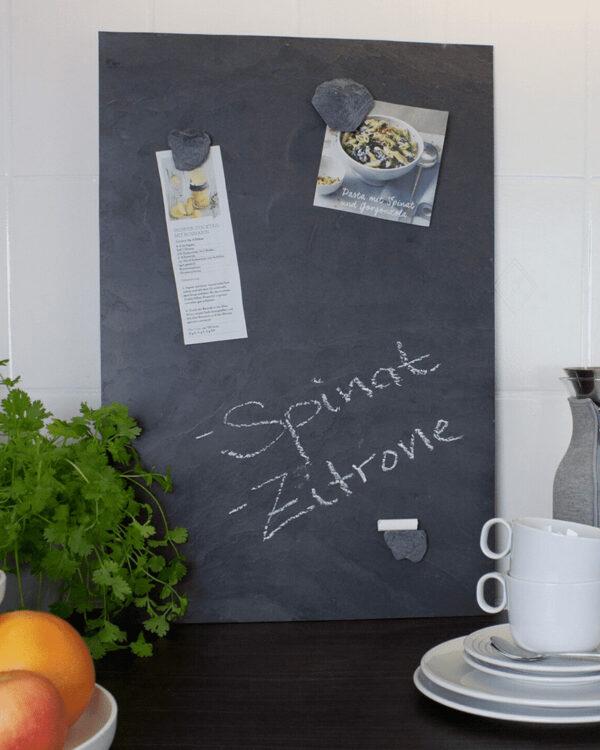 Magnetische Schiefer Kreidetafel in Anthrazit beschriftet mit Kreide und Magnetsteinen aufgestellt in der Küche