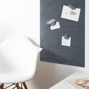 Schiefertafel magnetisch aufgehängt im Wohnzimmer und beschriftet mit Haftnotizen durch Magnetpins aus Schiefer